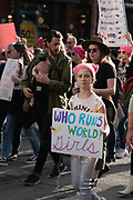 """San Francisco, USA. 19th January, 2019. At the Women's March San Francisco a young girl wearing a pink pussy hat marches with her sign reading, """"Who runs the world? Girls."""" Behind her a man marches while wearing a baby.  Credit: Shelly Rivoli/Alamy Live News"""