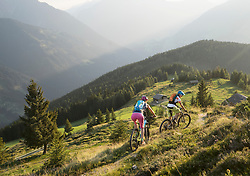 Mountain bikers riding on uphill in alpine landscape, Zillertal, Tyrol, Austria