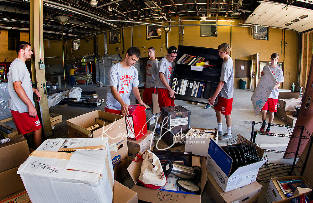 The entire Laconia Football team helped load furniture and supplies into storage during construction phase of the Laconia Fire Department on Friday morning.  (Karen Bobotas/for the Laconia Daily Sun)