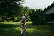 """MERIDIAN, MS – AUGUST 3, 2018: Clayton George, 57, passes near the old farm house where his father was raised. The home, which is now flanked on all sides by pine trees, reminds George of his family's heritage on the land stretching as far back as 1926. Now a resident of Tennessee, George makes the four hour drive south every two weeks to check in on the 400 acre tract, and visit his father who still lives there.<br /> <br /> In 1987, George and a friend walked in rows planting the family's first batch of Loblolly pine, where soybeans, wheat and cattle once covered the family's 400 acres.  The shift to timber was largely prompted by the Conservation Reserve Program, a popular new farm subsidy in the 1980s that encouraged farmers to reforest depleted land by paying them for every acre of trees planted. Since 1926, the George family had made a good living from their eastern Mississippi farm, but the decline of soybeans and other crops eventually led George to consider growing trees instead –a crop that landowners throughout the south believed would bring in easy money. Thirty years later, however, the same landowners are now facing unexpected financial hardship. Stumpage prices have been on a steady decline – as much as 45% since 2007 – and landowners are rethinking timber as a worthwhile investment. """"""""We figured we''d plant trees and come back and harvest it in 30 years, and in the meantime go into town to make a living doing something else,"""" George said. As co-owner of the family acreage with three other family members, George always considered himself the most nostalgic Now, as he patiently awaits for right time to harvest a 30 year investment, even he considers the future of the land uncertain. CREDIT: Bob Miller for The Wall Street Journal<br /> TIMBER_AL"""