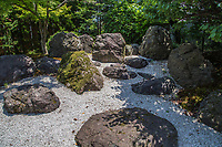 """Ichinomiyaji is Temple 83 on the Shikoku 88 Temple Pilgrimage trail. It's located next to an important Shinto shrine, Tamura Jinja to which it was once connected. There is a hole in the ground under the Yakushi Nyorai statue called the """"kettle of hell"""" which visitors are told that they can """"hear the sound of hell"""" inside.  At the entrance to Ichinomiya-ji there is a small rockery surrounded by a zen garden to greet visitors adjacent to ancient stone lanterns that once adorned the temple's original buildings."""