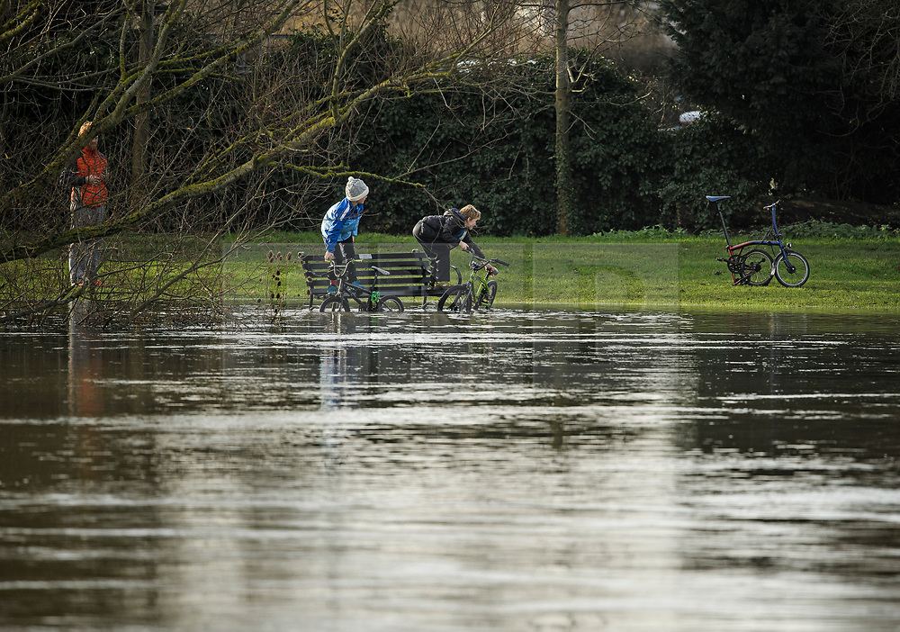 © Licensed to London News Pictures. 22/12/2019. Thames Ditton, UK. Children play on a flooded park bench the bank of The River Thames which has burst it's banks at Thames Ditton, Surrey. Further weather warnings are in place following flooding and high winds in parts of the UK . Photo credit: Ben Cawthra/LNP