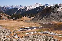 A partly frozen alpine tarn on Ophir Pass during the autumn season,  San Juan Mountains, Colorado.