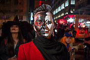 New York, NY - 31 October 2015. A woman in heavy black and white harlequin makeup in the annual Greenwich Village Halloween Parade.