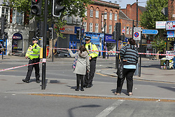 © Licensed to London News Pictures. 28/05/2021. London, UK. A member of public speaks with a police officer at a crime scene on High Road, Wood Green, north London, following a death of a man. Police were called at just after 1am on Friday, 28 May to reports of a firearm discharge in the vicinity of Turnpike Lane. Police officers, the London Ambulance Service and London's Air Ambulance attended the scene. A man, believed to be aged in his 20s, was found suffering a gunshot injury. Despite the efforts of the emergency services he was pronounced dead at the scene at just before 2am. Photo credit: Dinendra Haria/LNP