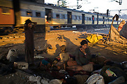 A mother and her children wake upon waste ground beneath a flyover near Okhla station as a train rushes past. New Delhi, India