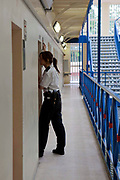 A young female prison officer checks the cells of each prisoner, making sure everything is in order.  Every bar is checked for breaks. YOI Aylesbury, Buckinghamshire, United Kingdom. HMYOI / HM Prison Aylesbury (Her Majesty's Young Offender Institution Aylesbury) is a prison is operated by Her Majesty's Prison Service.