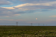 Full moon over plains with power polls. Near Rocky Ford CO