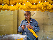12 JANUARY 2017 - BANGKOK, THAILAND:       A flower garland vendor at a Chinese Buddhist shrine in Bo Bae Market. Bo Bae Market is a sprawling wholesale clothing market in Bangkok. There are reportedly more than 1,200 stalls selling clothes made in Thailand and neighboring countries. Bangkok officials have threatened to shut down parts of Bo Bae market, but so far it has escaped the fate of the other street markets that have been shut down.     PHOTO BY JACK KURTZ