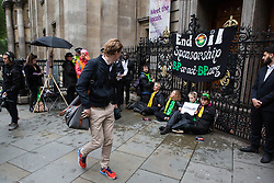 London, UK. 10 June, 2019. A passerby observes activists from BP or not BP? blocking access to the National Portrait Gallery in protest against BP's sponsorship of the BP Portrait Award. The energy company has sponsored the National Portrait Gallery's award for 30 years, but its high-profile involvement is attracting widespread criticism due to the intensifying focus on environmental issues. A number of artists, including previous award winners such as Wim Heldens and Craig Wiley, have called on the gallery to end its sponsorship by BP.