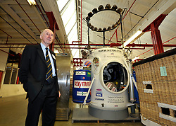© Licensed to London News Pictures. 28/02/2012. Don Cameron, founder of Cameron Balloons factory in Bedminster, Bristol, which manufactures hot air balloons for clients around the world.  They are seeking sponsorship for this year's Bristol International Balloon Fiesta which takes place in August.  Behind Don is the pressurised capsule for the Cameron Balloons World Altitude Record set by Indian businessman Dr Vojaypat Singhania who reached 69,852 feet over Mumbai in 2005..Photo credit : Simon Chapman/LNP