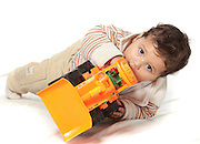 child of two playing with toy tractor On white Background