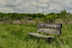 28 May 2014:   a single wood bench sits alone along the path through the north part of Moraine View State Park This image was produced in part utilizing High Dynamic Range (HDR) or panoramic stitching or other computer software manipulation processes. It should not be used editorially without being listed as an illustration or with a disclaimer. It may or may not be an accurate representation of the scene as originally photographed and the finished image is the creation of the photographer.