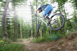 Mountain biker performing jump on bicycle on single track in forest, Bavaria, Germany