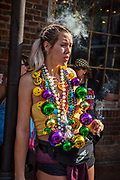 Young woman smoking a cigar and dressed to party on Boubon Street during Mardi Gras on 25th February 2020 in New Orleans, Louisiana, United States. Mardi Gras is the biggest celebration the city of New Orleans hosts every year. The magnificent, costumed, beaded and feathered party is laced with tradition and  having a good time. Celebrations are concentrated for about two weeks before and culminate on Fat Tuesday the day before Ash Wednesday and Lent.