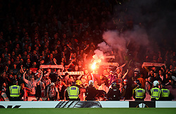 Fans let off flares in the stands during the match