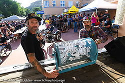 Custom bike builder and event organizer JP Rodman and Slinging Ink tattoo artist Oliver Peck turn the raffle barrel during the Run to Raton. Raton, NM. USA. Saturday July 21, 2018. Photography ©2018 Michael Lichter.