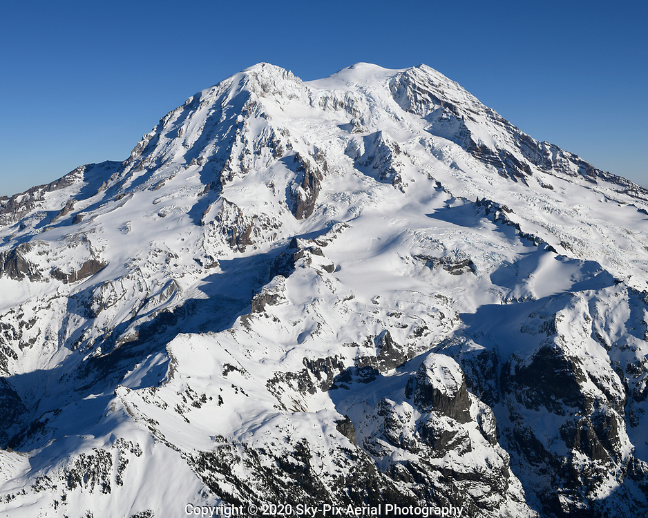 The summit of Mt Rainier with its three peaks at the top: Liberty Cap (left), Columbia Crest (middle), and Point Success (right). Below Liberty Cap are Mowich Face and Sunset Amphitheater, which are separated by Sunset Ridge on the western flank of the volcano. The glaciers from left to right are: Edmunds Glacier, South Mowich Glacier, Puyallup Glacier, and Tahoma Glacier.