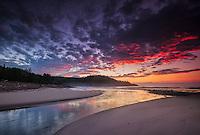 Colorful clouds light up at sunrise along the coastline of Cape Breton island, Nova Scotia, Canada