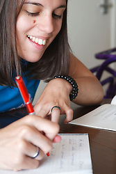 Young woman with Cerebral Palsy, who uses a walking frame, studying.