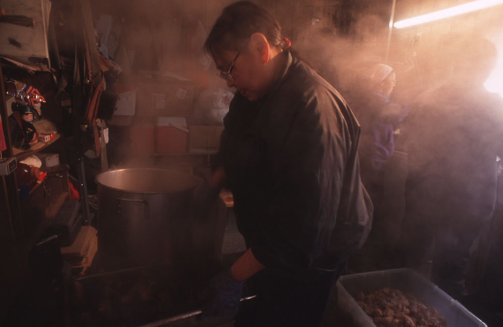 At the garage of Captain Edward Itta's house, Denise Varner cook whale meat for the feast where the whole town is invited to get some shares at the captain's house.  <br /> <br /> May 14, 11:40