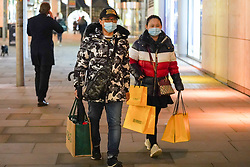© Licensed to London News Pictures. 30/12/2020. Manchester, UK.  Shoppers wearing face masks carry several shopping bags as they  walk in Manchester City  ahead of Tier 4 restrictions come into force. The county of Greater Manchester from Thursday 31 December will move into Tier 4 following a spike in coronavirus cases. Photo credit: Ioannis Alexopoulos/LNP