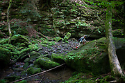 Wearing a peaked cap and small rucksack, a young adventurer, scales a giant boulder in the ancient forest of Monbachtal Bach in Germany's Black Forest. Stretching to climb the rock, the lad of 10 uses his hand and walking stick to balance as he puts a boot higher to gain a sure footing. There is ample covering of moss and lichen on the primeval landscape making it hazardous to conquer but the boy has the stamina to get to the top and continue his walk through this beautiful wilderness. The boy is alone in the picture though accompanied by his family but he seems to mange on his own, capable of finding his own limits of endurance and confidence. Geologically, the Black Forest consists of a cover of sandstone on top of a core of gneiss. During the last glacial period, the Würm glaciation, the Black Forest was covered by glaciers.