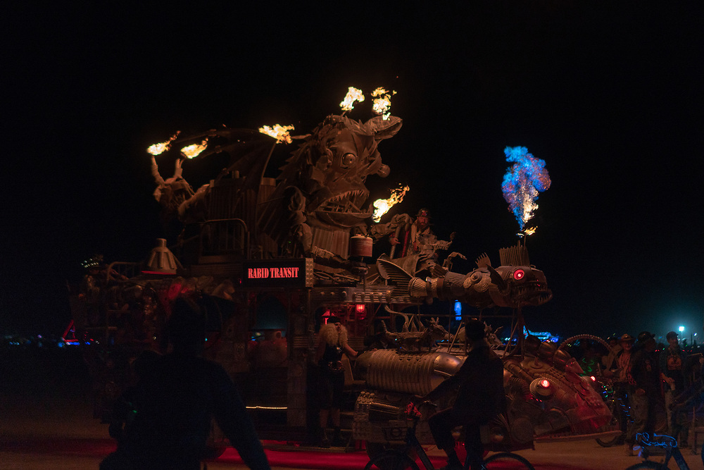 """by Duane Flatmo and crew. (If you time it right you can catch a photo of the flame while it is blue! Notice the man on the """"hood"""" area. I presume he is going to re-ignite the flame there.) My Burning Man 2018 Photos:<br /> https://Duncan.co/Burning-Man-2018<br /> <br /> My Burning Man 2017 Photos:<br /> https://Duncan.co/Burning-Man-2017<br /> <br /> My Burning Man 2016 Photos:<br /> https://Duncan.co/Burning-Man-2016<br /> <br /> My Burning Man 2015 Photos:<br /> https://Duncan.co/Burning-Man-2015<br /> <br /> My Burning Man 2014 Photos:<br /> https://Duncan.co/Burning-Man-2014<br /> <br /> My Burning Man 2013 Photos:<br /> https://Duncan.co/Burning-Man-2013<br /> <br /> My Burning Man 2012 Photos:<br /> https://Duncan.co/Burning-Man-2012"""