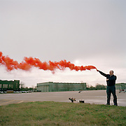 Engineering ground staff member of the Red Arrows, Britain's RAF aerobatic team, tests red smoke canister in regular procedure.