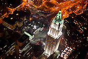 Aerial photograph of the Woolworth Building at night, with City Hall and the Brooklyn bridge entrance in the background.