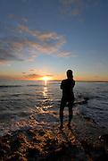 Young woman enjoying a beautiful sunset at Migjorn beach, Formentera