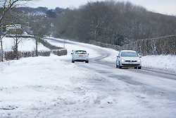 Licensed to London News Pictures. 13/01/2017. Warlingham, UK. Cars pass on an icy road near Botley Hill in Surrey today (13/01/2017) after heavy snowfall hit parts of the UK yesterday. Many roads were rendered impassable with some drivers being forced to abandon their vehicles. Photo credit: Matt Cetti-Roberts/LNP