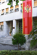 Skupstina Republica Crna Gora, the parliament assembly of Montenegro, main entrance with glass, brass and stone, on the Sveti Petra Saint Peter boulevard. The Montenegrin flag banner in the foreground, red with golden eagle. Podgorica capital. Montenegro, Balkan, Europe.