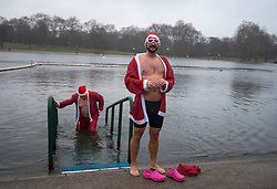 © Licensed to London News Pictures. 25/12/2017. London, UK. Two men in Santa suits take a dip before Members of the Serpentine Swimming Club brave the cold waters at the Serpentine Lake in Hyde Park, London to compete for the traditional Peter Pan Cup on Christmas Day, December 25, 2017. Photo credit: Ben Cawthra/LNP