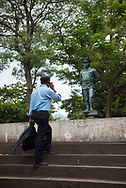 Kandy, Sri Lanka - April, 3, 2017: A pedestrian emerges from an underground street crossing while talking on his mobile phone. The statue is of Lieutenant General Denzil Lakshman Kobbekaduwa, born in Kandy in 1940 and killed during the Sri Lankan Civil War in 1992.