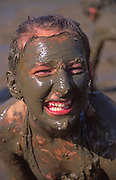 A073WH Girl child smiling playing in thick mud with body covered by brown mud