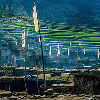 Tibetan Buddhis prayer flags fly above houses in remote Manang village, north of Annapurna in Nepal.