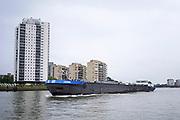 Nederland, the Netherlands, Rotterdam, 30-7-2017Een binnenvaartschip vaart langs woontorens, flats, richting Dordrecht vanuit de haven van Rotterdam.Foto: Flip Franssen