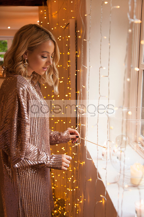 Woman Lighting Candle by Window