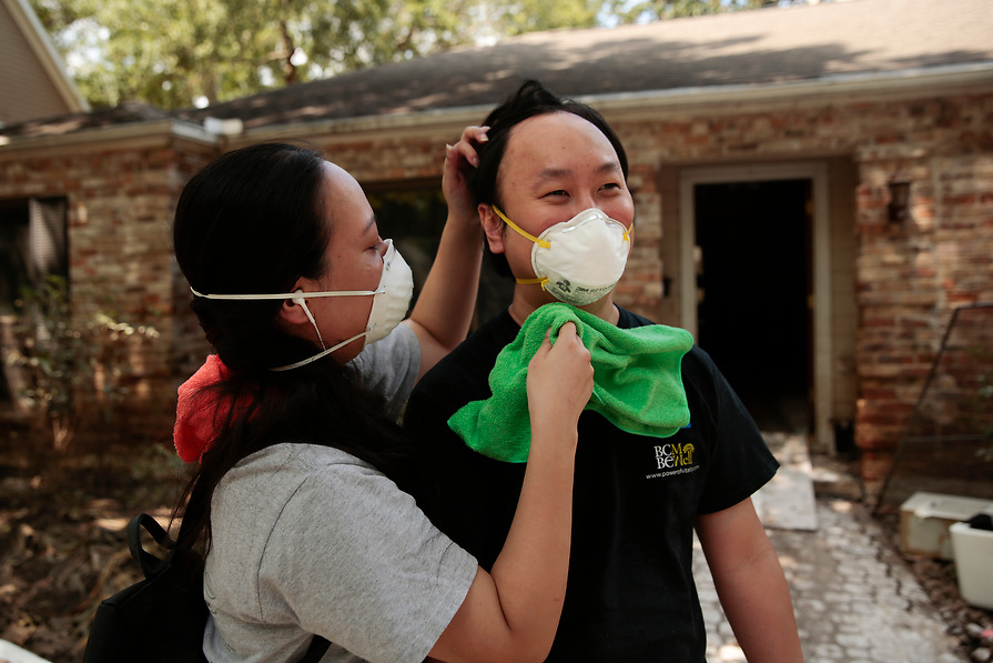 """Vera Hsiung cleans off her husband, Elliot Wu's, neck and face as they clean out their home which was flooded with water for twelve days in the aftermath of tropical storm Harvey in west Houston, Texas, U.S. September 11, 2017. """"We're really worried about contacting disease from exposure to mold,"""" said Hsiung.  Their home flooded after controlled releases from Addicks Reservoir and neighboring Barker reservoir."""