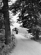 This scene along route 99 shows Oregon's principal north-south interstate highway before divided highways bypassed or replaced them. Almost any trip through Western Oregon would take you through covered bridges, or on ferries across the larger rivers. There used to be hundreds of covered bridges in Oregon, and now only about fifty remain. This is the Quines Creek Covered Bridge over Cow Creek near Azalea, in Douglas County, Oregon. It exhibits damage over the portal resulting from a high-loaded logging truck. The bridge was built in 1913 and collapsed in 1958. Highway 99 was replaced here by I-5 and the covered bridge location is where the exit ramp feeds Quines Creek Road and crosses Cow Creek. The photographer noted that he took this picture in the mist of dawn before sunrise, August 10, 1949.