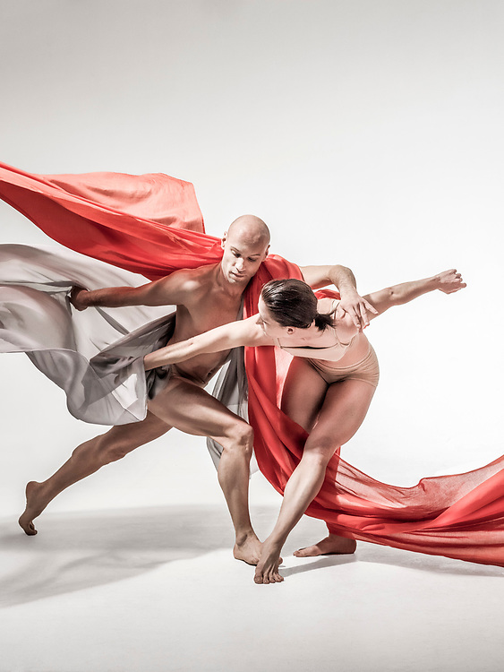 Dancers with red and grey scarfs dancing in a studio