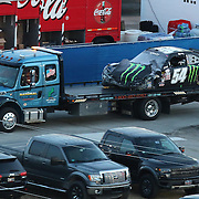The wrecked car of Kyle Busch (54) is transported back to the garage  after crashing during the Alert Today Florida 300 XFinity Series race at Daytona International Speedway on Saturday, February 21, 2015 in Daytona Beach, Florida. It has been reported Busch has a broken leg and will not race in the 2015 Daytona 500 race. (AP Photo/Alex Menendez)