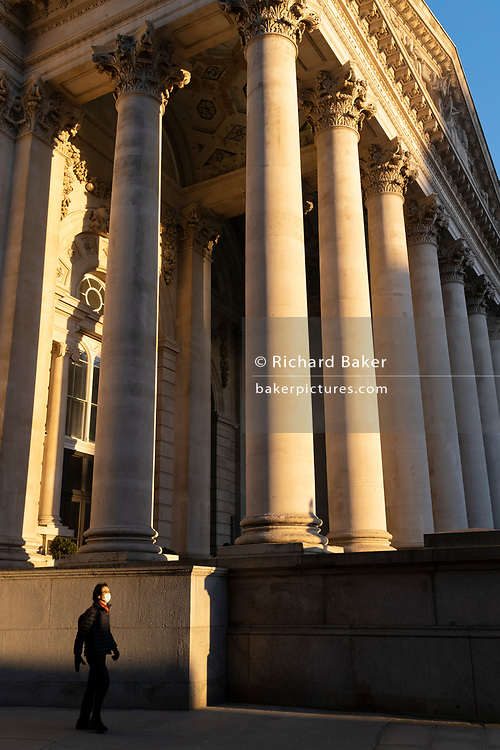 With most Londoners still working from home, a commuter walks beneath the columns of Royal Exchange while walking along a quiet Threadneedle Street during the evening rush-hour during the third lockdown of the Coronavirus in the City of London, the capital's financial district, on 26th February 2021, in London, England. At the top of Doric and Ionic columns with their ornate stonework, powerfully strong lintels cross, bearing the load of fine artistry and carvings which feature the design by Sir William Tite in 1842-1844 and opened in 1844 by Queen Victoria whose name is written in Latin (Victoriae R). It's the third building of the kind erected on the same site. The first Exchange erected in 1564-70 by sir Thomas Gresham but was destroyed in the great fire of 1666. It's successor, by Jarman, was also burned down in 1838. The present building is grade 1 listed and cost about £150,000.