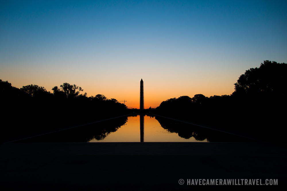 Just before dawn, the light illumates the sky behind a silhouette of the Washington Monument, with the Reflecting Pool in the foreground.