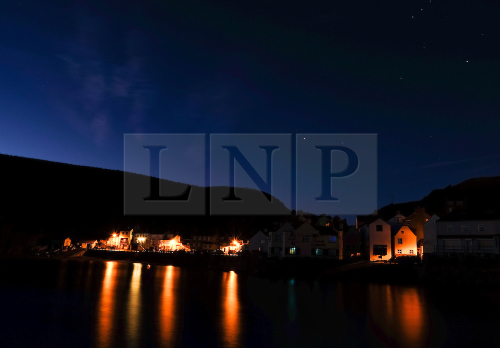 © Licensed to London News Pictures.02/10/15<br /> Staithes, UK. <br /> <br /> Street lights reflect in water in the harbour as dawn breaks in the North Yorkshire village of Staithes on the east coast as the warm autumn weather continues.<br /> <br /> Photo credit : Ian Forsyth/LNP