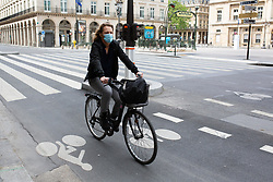 Cyclist wearing face mask on Rivoli Street in Paris on May 4, 2020, on the forty-ninth day of a strict lockdown in France, in place to attempt to stop the spread of the new coronavirus (COVID-19). Photo by Raphael Lafargue/ABACAPRESS.COM