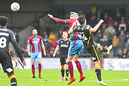 Matthew Lund of Scunthorpe United (7) heads above Danny Devine of Bradford City (24) during the EFL Sky Bet League 1 match between Scunthorpe United and Bradford City at Glanford Park, Scunthorpe, England on 27 April 2019.