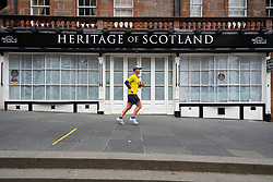 Edinburgh, Scotland, UK. 24 March, 2020.  Deserted streets in the heart of the Old Town tourist district in Edinburgh. All shops and restaurants are closed with very few people venturing outside following the Government imposed lockdown today. Pictured; Runner passes a closed and covered up tourist gift shop on the Royal Mile. Iain Masterton/Alamy Live News