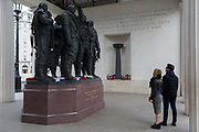 A young couple admire the Bomber Command War Memorial on 16th March 2017, in Green Park, London, England. The 9-foot 2.7 m bronze sculpture of seven aircrew, designed by the sculptor Philip Jackson look as though they have just returned from a bombing mission and left their aircraft. The figures represent L-R: Navigator, Flight Engineer, Mid-upper gunner, Pilot, Bomb aimer, Rear gunner and Wireless operator. The Royal Air Force Bomber Command Memorial is a memorial in Green Park, London, commemorating the crews of RAF Bomber Command who embarked on missions during the Second World War. The memorial was built to mark the sacrifice of 55,573 aircrew from Britain, Canada, Czechoslovakia, Poland and other countries of the Commonwealth, as well as civilians of all nations killed during raids. Queen Elizabeth II unveiled the memorial on 28 June 2012, the year of her Diamond Jubilee.